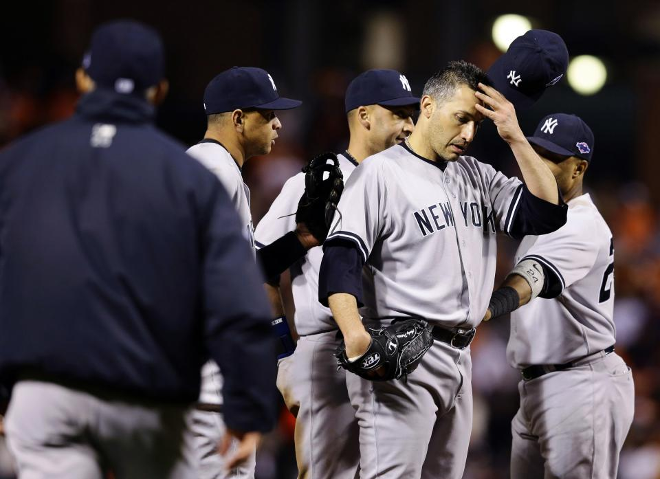 New York Yankees starting pitcher Andy Pettitte removes his cap as manager Joe Girardi, far left, walks out to relieve him in the eighth inning of Game 2 of the American League division baseball series against the Baltimore Orioles, Monday, Oct. 8, 2012, in Baltimore. Baltimore won 3-2. (AP Photo/Alex Brandon)