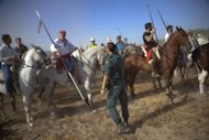 "A Spanish civil guard gives instructions to men riding horses during the ""Toro de la Vega"" festival in Tordesillas. At least one horseman speared the bull in a fatal strike by the bridge, an AFP photographer saw, but the lancing took place outside the official area, so the tournament was declared null"