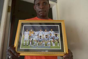 Beliby Ferdinand Bengondo holds a picture of his late …