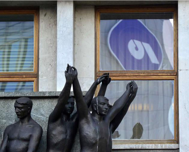A logo of Ljubljanska Banka is reflected in the window of Slovenia's parliament building in Ljubljana