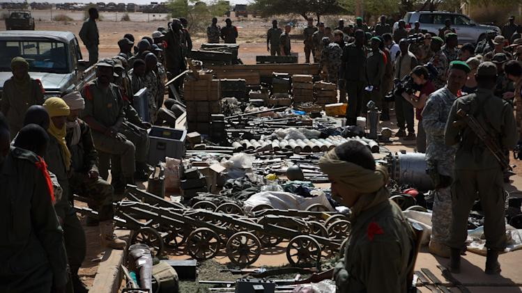 Malian soldiers look on as weapons, munitions, and other paraphernalia seized from radical Islamist rebels, are displayed at the French army base in Gao, Mali, Sunday, Feb. 24, 2013. The Chadian army said Saturday that its troops had killed 65 Islamic extremist rebels and destroyed five vehicles in the Adrar des Ifoghas mountains of northeastern Mali. According to the statement, 13 Chadian soldiers were also killed and six were wounded in the fighting Friday.(AP Photo)