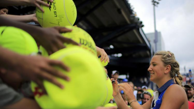 Victoria Azarenka of Belarus signs autographs after defeating Elena Vesnina of Russia at the 2014 U.S. Open tennis tournament in New York