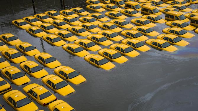 FILE - In this Oct. 30, 2012 file photo, a parking lot full of yellow cabs is flooded as a result of Superstorm Sandy in Hoboken, NJ. An internal review says federal weather forecasts for Superstorm Sandy were exceptionally accurately last fall. But the warnings themselves were confusing. The gigantic October storm lost tropical characteristics hours before landfall in New Jersey, so the National Oceanic and Atmospheric Administration dropped the hurricane warnings. Instead it shifted to flooding and high wind warnings. NOAA's self-assessment said that led to confusion by the public and the media, a complaint made by independent meteorologists.  (AP Photo/Charles Sykes, File)