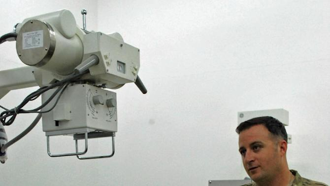 U.S. Army Staff Sgt. Nathan Lethgo, of the 101st Airborne Division, stands next to an X-ray machine on Saturday, May 26, 2013, at the Afghan National Army's medical clinic on Camp Parsa in Khost Province, Afghanistan. The machine hasn't been working for three months and Lethgo is trying to help the Afghans figure out the solution. As Afghan forces take over fighting this year, the Afghan National Army is struggling with a shortage of doctors. (AP Photo/Kristin M. Hall)
