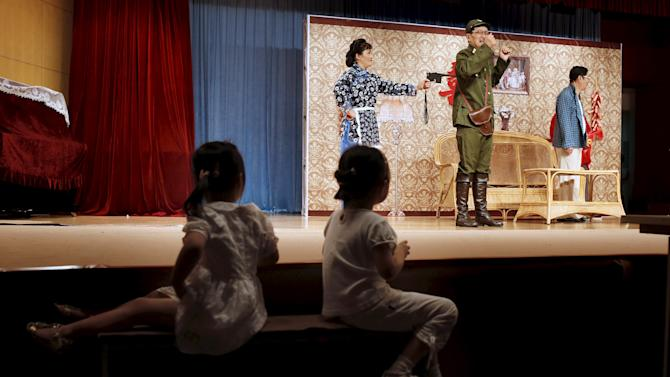 Girls watch a performance by a man with Japanese military uniform during a Chinese opera show during an event to mark the 70th anniversary of the end of the Sino-Japan War in Shanghai