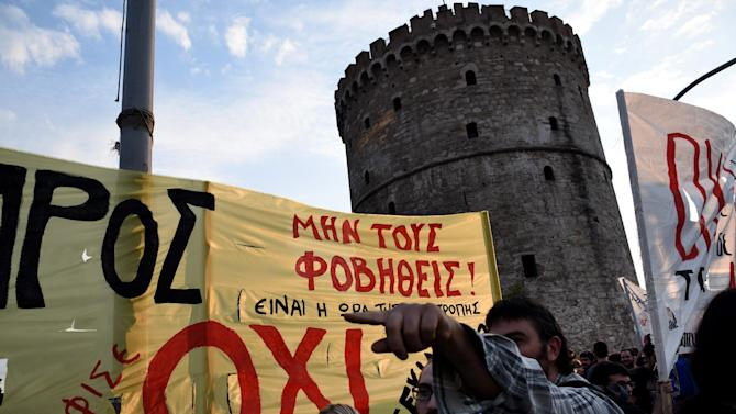 A demonstrator gestures in front of a banner reading ''NO, not to fear'' during a rally by supporters of the no vote to the upcoming referendum in the northern Greek port city of Thessaloniki, Wednesday, July 1, 2015. Eurozone finance ministers decided Wednesday to break off talks on more aid for Greece until after it holds a weekend referendum, even as the Greek government pressed ahead with plans to let the people decide whether to accept more austerity measures in exchange for a rescue deal. (AP Photo/Giannis Papanikos)