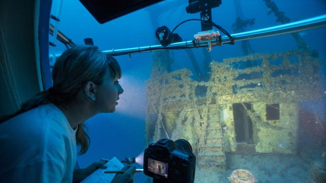 """In this Friday, June 28, 2013 photo, Oregon State University lionfish expert Stephanie Green counts lionfish on the sunken freighter """"Bill Boyd,"""" as she travels aboard the submersible """"Antipodes,"""" in about 250 feet under the sea about three miles off the coast of Fort Lauderdale, Fla. Seattle-based OceanGate Inc. offered scientists and wildlife officials a close-up look at the invasive lionfish deep in the waters off South Florida aboard the Antipodes. Divers in Florida and the Caribbean are encouraged to capture and eat any lionfish they encounter to protect reefs and native marine life already burdened by pollution, over-fishing and the effects of climate change. Recreational divers max out around 130 feet and researchers and wildlife officials rarely have the means to go looking for lionfish deeper than that, but they've realized that the lionfish they can't see may be their biggest concern. (AP Photo/Wilfredo Lee)"""