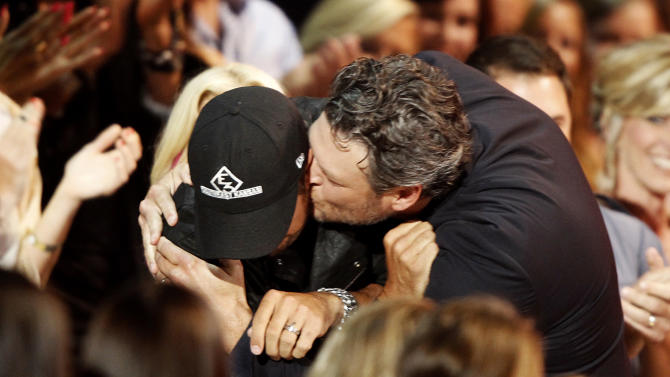 "Blake Shelton, right, kisses Luke Bryan in the audience as he walks to the stage to accept his award for male video of the year for ""Doin' What She Likes"" at the CMT Music Awards at Bridgestone Arena on Wednesday, June 4, 2014, in Nashville, Tenn. (Photo by Wade Payne/Invision/AP)"