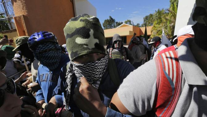 Masked CETEG members protest outside the Governor's official residence as they demand the government find the missing students of the Ayotzinapa Teacher Training College Raul Isidro Burgos in Iguala, in Chilpancingo