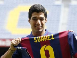 FC Barcelona's Luis Suarez holds up his jersey during his presentation at the Nou Camp stadium in Barcelona