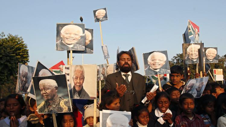 Pakistani Christians hold placards bearing the image of former South African President Nelson Mandela as they gather to pay tribute to Mandela in Islamabad