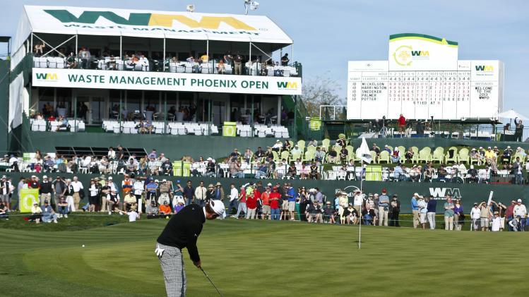 With the gallery in the background, Jeff Overton putts onto the 18th green during the first round of the Waste Management Phoenix Open golf tournament Thursday, Jan. 31, 2013, in Scottsdale, Ariz.(AP Photo/Ross D. Franklin)