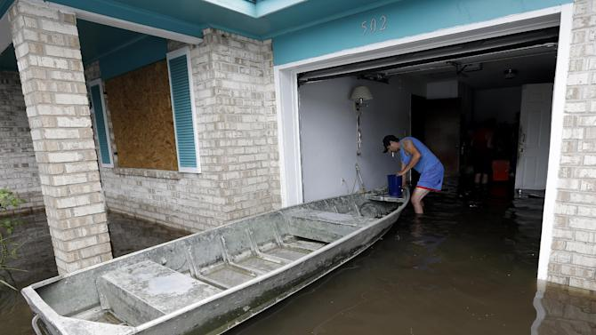 Anthony Tabb ties off a boat in his uncles flooded home as they work to recover personal items, Friday, Aug. 31, 2012, in LaPlace, La. Isaac crawled into the central U.S. on Friday, leaving behind a soggy mess in Louisiana.  It will be a few days before the water recedes and people in flooded areas can return home. New Orleans itself was spared, thanks in large part to a levee system fortified after Katrina devastated the Gulf Coast in 2005.  (AP Photo/Eric Gay)
