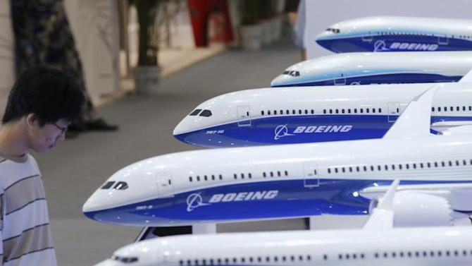 A visitor looks at a display of miniature Boeing passenger aircraft at Aviation Expo China 2013 in Beijing