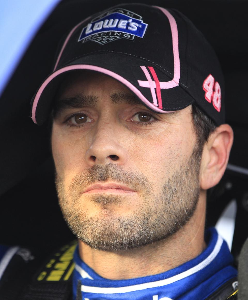 Jimmie Johnson sits in his car as he looks at results during qualifying for Sunday's NASCAR Sprint Cup Series auto race at Martinsville Speedway in Martinsville, Va., Friday, Oct. 26, 2012. Johnson won the pole. (AP Photo/Steve Helber)