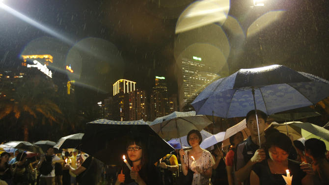 People attend a candlelight vigil under heavy rain at Victoria Park in Hong Kong Tuesday June 4, 2013 to mark the 24th anniversary of the June 4th Chinese military crackdown on the pro-democracy movement in Beijing. (AP Photo/Vincent Yu)