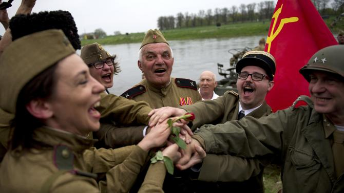 Members of a historical re-enactment group dressed as U.S. and Soviet Army soldiers take part in 'Elbe Day' celebrations in Torgau