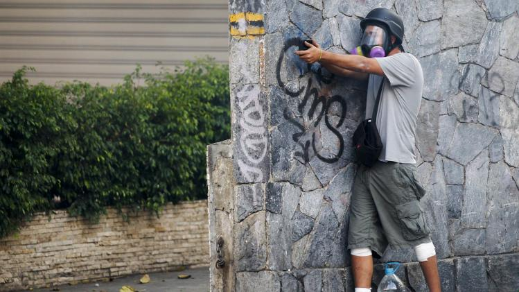 An anti-government protester holds up his hands in a gun-holding pose during a protest in Caracas