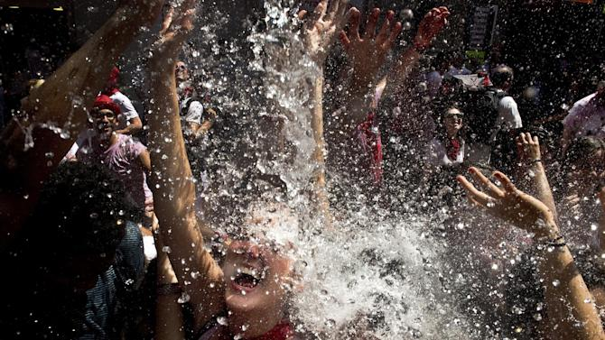 Revellers cool off with water thrown from a balcony at the start of the San Fermin festival in Pamplona