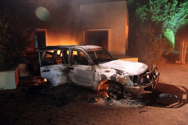 A vehicle and surrounding buildings smolder after they were set on fire inside the US consulate compound in Benghazi late on September 11, 2012. An armed mob protesting over a film they said offended