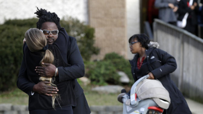 Mourners hug after leaving the church where Jovan Belcher's funeral was held in Dix Hills, N.Y., Wednesday, Dec. 12, 2012. Several hundred mourners have gathered for the funeral of Kansas City Chiefs linebacker Jovan Belcher near his hometown on Long Island. The 25-year-old Belcher shot and killed his girlfriend and then himself Dec. 1. (AP Photo/Seth Wenig)