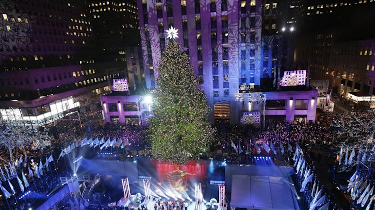 The Rockefeller Center Christmas tree is lit during a ceremony, Wednesday, Dec. 4, 2013, in New York. Some 45,000 energy efficient LED lights adorn the 76-foot tree. (AP Photo/Kathy Willens)