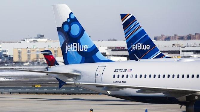 An airport worker leads JetBlue planes onto the tarmac of the John F. Kennedy International Airport in New York