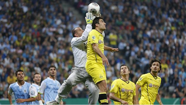 Munich's Garbor Kiraly, left, and Dortmund's Sokratis of Greece challenge for the ball during the German soccer cup second round match between TSV 1860 Munich and Borussia Dortmund, in Munich, souther