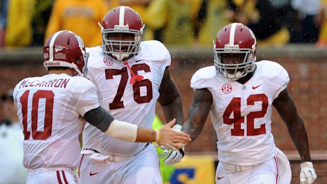 Alabama quarterback AJ McCarron (10) and offensive linesman D.J. Fluker (76) congratulate teammate Eddie Lacy on his 73-yard touchdown run during the first quarter of an NCAA college football game against Missouri, Saturday, Oct. 13, 2012, in Columbia, Mo. (AP Photo/L.G. Patterson)