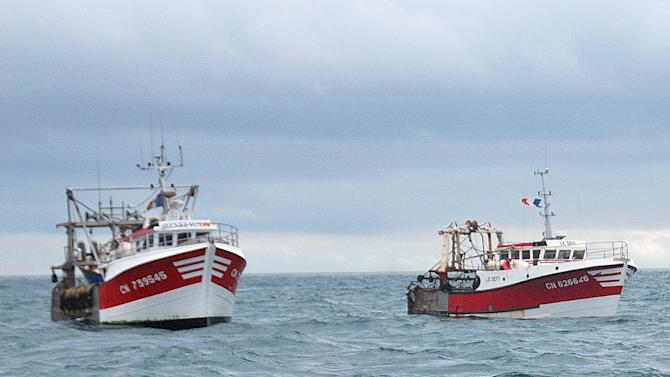 This Oct. 8, 2012 photo shows, French fish boats with their flags at half mast, as they prevent British fish boats, unseen, to fish, in the English Channel, off Le Havre, western France. A bumper season for the French national dish of Coquilles St. Jacques has turned into a bitter dispute in the English Channel, as French fishermen angry over British expansion into their waters surrounded British boats in a show of maritime force.(AP Photo/Pierre Guillaume)