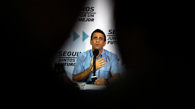 The silhouette of a videographer and his camera frame Venezuela's opposition leader Henrique Capriles as he recites a passage from the national constitution during a news conference in Caracas, Venezuela, Tuesday, Jan. 8, 2013. Capriles said that the Supreme Court should rule in a dispute between the opposition and President Hugo Chavez's government over whether the ailing leader's inauguration can legally be postponed. Capriles said the constitution is clear that the current presidential term ends on Jan. 10. Chavez remains in Havana after undergoing his fourth cancer surgery on Dec. 11 and hasn't spoken publicly in a month. (AP Photo/Fernando Llano)