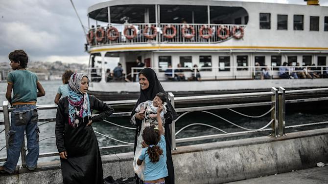 A newly-arrived Syrian refugee woman holds her baby as she stands with her family at Eminonu in Istanbul on August 18, 2014