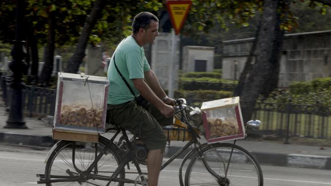A street vendor rides his bicycle carrying donuts in Havana, Cuba, Tuesday, Nov. 13, 2012. The U.N. General Assembly on Tuesday voted overwhelmingly to condemn the U.S. commercial, economic and financial embargo against Cuba for the 21st year in a row. The embargo was first enacted in 1960 following Cuba's nationalization of properties belonging to U.S. citizens and corporations. (AP Photo/Franklin Reyes)