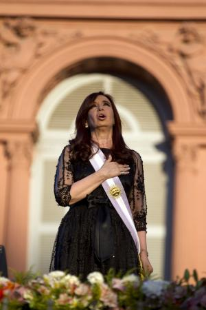 FILE - In this Dec. 10, 2011 file photo, Argentina's President Cristina Fernandez sings her country's national anthem after her swearing-in ceremony outside the government house in Buenos Aires, Argentina. Both supporters and opponents of Fernandez are invoking the threat of a constitutional change to allow a third consecutive presidential term. Fernandez has no interest in appearing to be a lame duck, and analysts say her silence on the question has helped her thwart would-be challenges to her near-absolute power. (AP Photo/Natacha Pisarenko, File)
