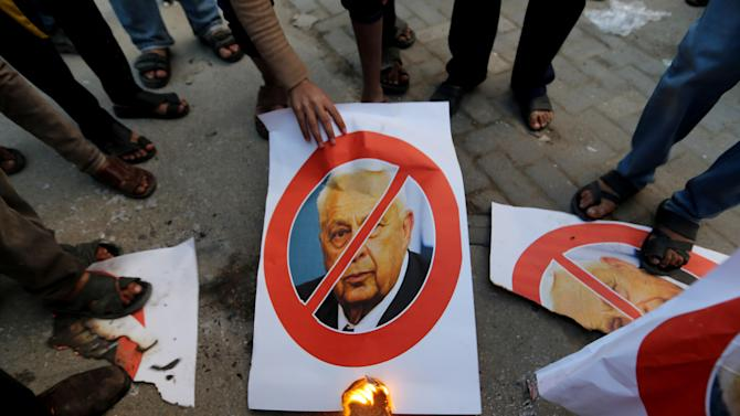 Palestinians stand over pictures of the former Israeli Prime Minister Ariel Sharon as another holds a burning poster of him in Khan Younis, southern Gaza Strip, Saturday, Jan. 11, 2014. Sharon was loathed by many Palestinians as a bitter enemy who did his utmost to sabotage their independence hopes — by leading military offensives against them in Lebanon, the West Bank and Gaza and a settlement drive on the lands they want for a state. Sharon died Saturday, eight years after a debilitating stroke put him into a coma. He was 85. (AP Photo/Hatem Moussa)