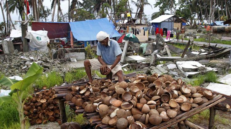Ereneio Dagami, who lost his house during typhoon Haiyan a month ago, grates coconuts at the battered town of Catadman