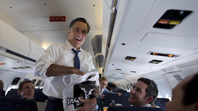 Republican presidential candidate, former Massachusetts Gov. Mitt Romney laughs as he hands out beef jerky to the press on his campaign plane, Friday, Sept. 28, 2012, in Philadelphia.  (AP Photo/ Evan Vucci)