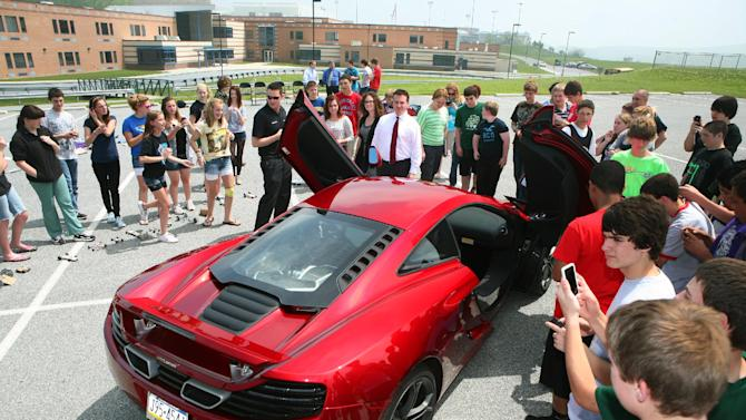 Eighth graders from Twin Valley Middle School gather around the new McLaren MP4-12C supercar at the middle school in Elverson, Pa. Friday, May 4, 2012. Students from the school who have been applying various aspects of the supercar to their studies in language arts, mathematics and science, finally got to meet the car in person. (Mark Stehle/AP Images for McLaren Automotive)
