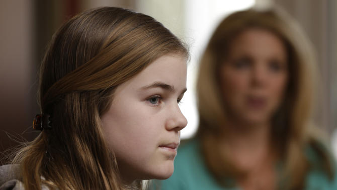 """Caroline Pla, 11, accompanied by her mother Marycecelia """"Seal"""" Pla, listens to a question during an interview Thursday, Feb. 21, 2013, in Doylestown, Pa. The Plas are fighting the Roman Catholic Archdiocese of Philadelphia for the right to continue playing church sponsored youth football. (AP Photo/Matt Rourke)"""