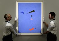 "Gallery assistants pose with artist Joan Miro's ""Peinture (Etolie Bleue), 1927"" at Sotheby's auction house in central London on June 14. The masterpiece sold at a London auction for over £23 million, an auction record for the artist"