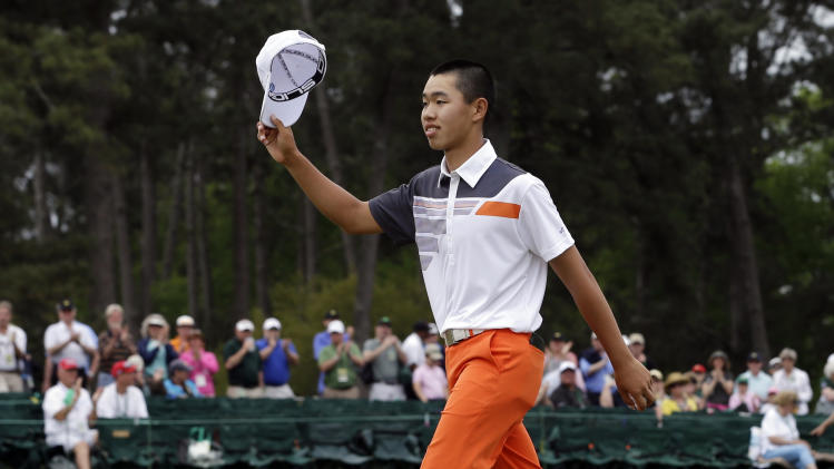 Amateur Guan Tianlang, of China, waves his cap after putting out on the 18th hole during the fourth round of the Masters golf tournament Sunday, April 14, 2013, in Augusta, Ga. (AP Photo/David J. Phillip)
