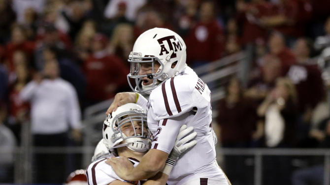 Texas A&M quarterback Johnny Manziel, right, celebrates his touchdown run with offensive linesman Luke Joeckel (76) in the first half of the Cotton Bowl NCAA college football game against Oklahoma on Friday, Jan. 4, 2013, in Arlington, Texas. (AP Photo/Tony Gutierrez)