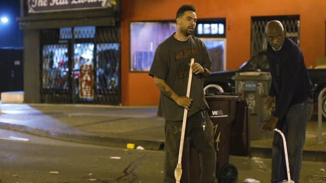 Two residents clean up trash left by protesters during a demonstration in Oakland, California