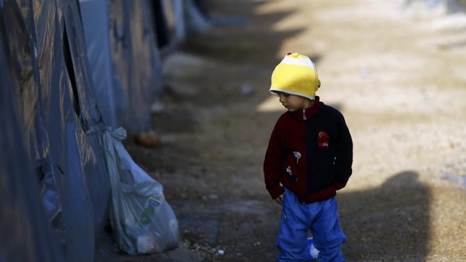 A Kurdish refugee child from the Syrian town of Kobani walks in a camp in the southeastern town of Suruc