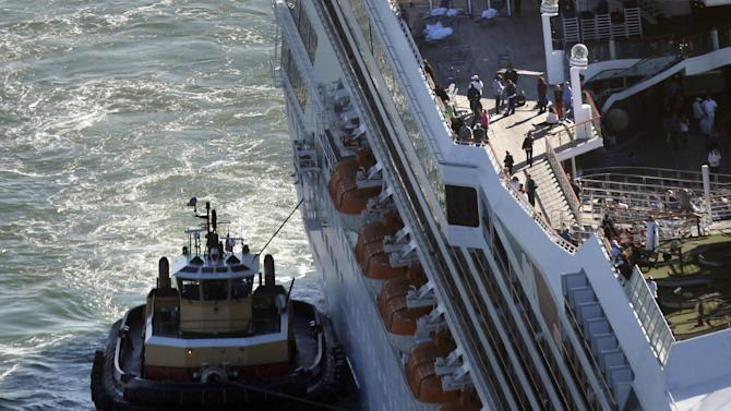 In this aerial photo, the cruise ship Carnival Triumph is towed into Mobile Bay, Ala. Thursday, Feb. 14, 2013. The ship with more than 4,200 passengers and crew members has been idled for nearly a week in the Gulf of Mexico following an engine room fire. (AP Photo/Gerald Herbert)