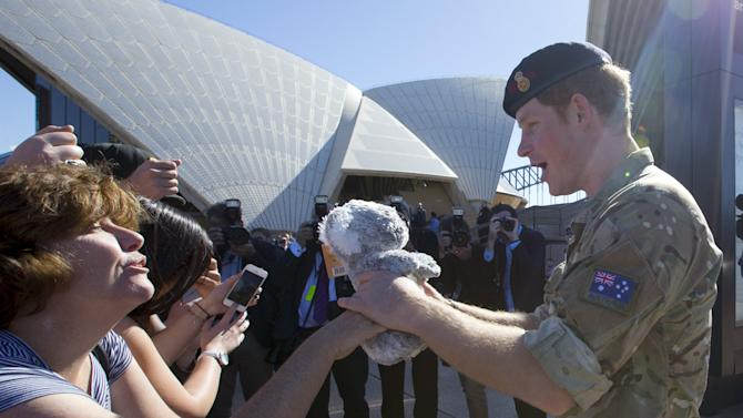 Britain's Prince Harry receives a toy koala from Anne Woods as he greets well-wishers during a visit to Sydney's Opera House in Australia