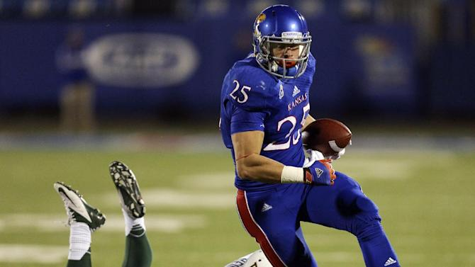 Kansas Jayhawks running back Brandon Bourbon (25) slips past Baylor Bears cornerback Ryan Reid for a touchdown in the third quarter of an NCAA college football game Saturday, Oct. 26, 2013, in Lawrence, Kan. Baylor won 59-14