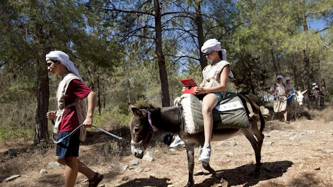 American tourist Ella uses an iPad while riding a Wi-Fi-outfitted donkey lead by her brother Aaron, in Kfar Kedem, a biblical reenactment park in the village of Hoshaya in the Galilee, northern Israel, Wednesday, Aug. 22, 2012. Visitors riding donkeys through the Old Testament landscape can now also surf the web while being transported across the land of the Bible. Organizers are hoping to connect the younger generation to ancient Galillee life while allowing them to like, share, tweet and snap it instantly to their friends. (AP Photo/Ariel Schalit)