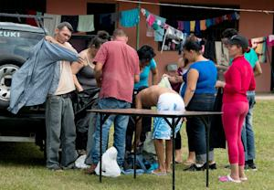 Cubans from a group of 150 receive clothes in a shelter…