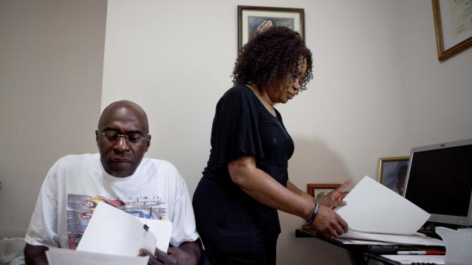 Michael, left, and Patricia Jackson sift through bank documents in their home Saturday, June 16, 2012, in Marietta, Ga. On a suburban cul-de-sac northwest of Atlanta, the Jacksons are struggling to keep a house worth $100,000 less than they owe. Their voices and those of many others tell the story of a country that, for all the economic turmoil of the past few years, continues to believe things will get better. But until it does, families are trying to hang on to what they've got left. The Great Recession claimed nearly 40 percent of Americans' wealth, the Federal Reserve reported last week. The new figures, showing Americans' net worth has plunged back to what it was in 1992, left economists shuddering. (AP Photo/David Goldman)